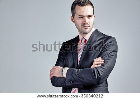 Confident businessman with arms crossed isolated over grey - stock photo
