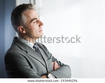 Confident businessman with arms crossed looking through a window. - stock photo