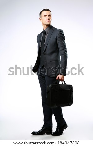 Confident businessman with bag looking away over gray background - stock photo