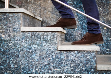 Confident businessman with bag walking the stairs - stock photo
