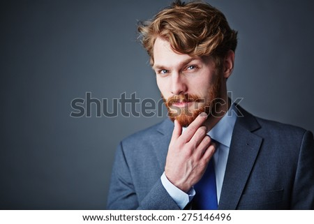 Confident businessman with beard looking at camera - stock photo