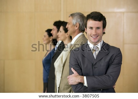 Confident businessman with team behind him - stock photo