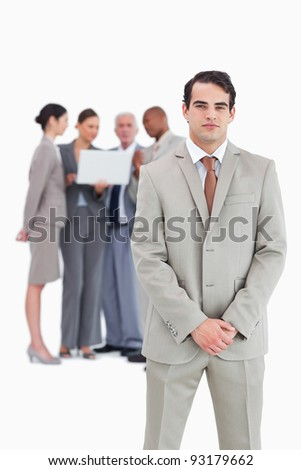 Confident businessman with team behind him against a white background - stock photo