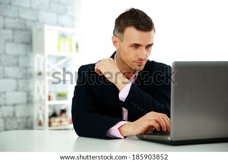 Confident businessman working on a laptop at office - stock photo