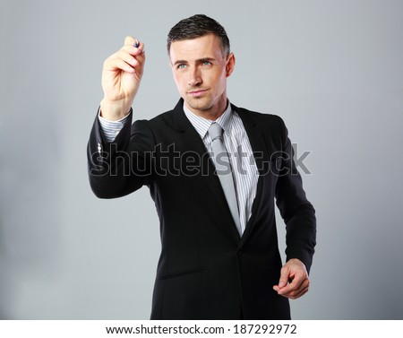 Confident businessman writes with pen at copyspace on gray background - stock photo