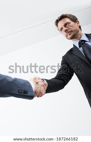 Confident businessmen shaking hands with empty white room on background. - stock photo