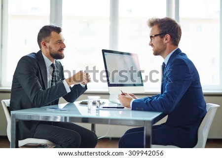 Confident businessmen sitting by table during consultation