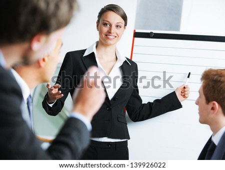 Confident businessowman giving a presentation on whiteboard - stock photo