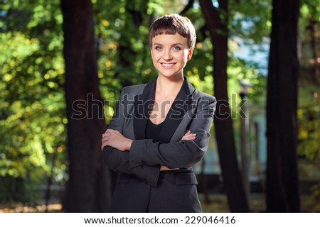 Confident businesswoman. Attractive young smiling businesswoman in formal wear keeping arms crossed and looking at camera outdoors - stock photo