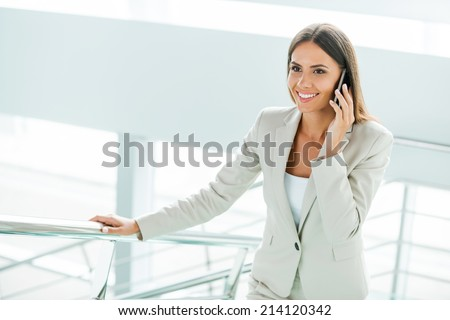 Confident businesswoman. Beautiful young businesswoman in formalwear talking on the mobile phone and smiling while moving up by staircase - stock photo