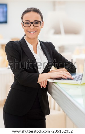 Confident businesswoman. Beautiful young woman in formalwear working on laptop and smiling while leaning at bar counter - stock photo