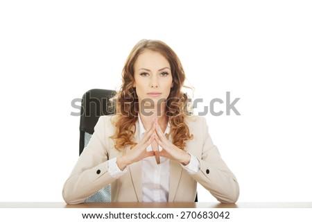 Confident businesswoman by a desk. - stock photo