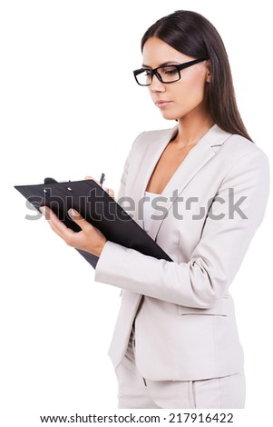 Confident businesswoman. Confident young businesswoman writing something in clipboard while standing isolated on white - stock photo