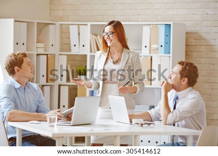 Confident businesswoman explaining her idea to co-workers in office