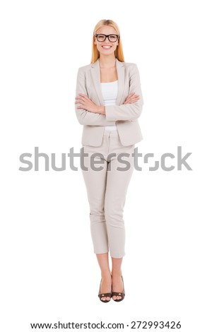 Confident businesswoman. Full length of beautiful young woman in formalwear keeping arms crossed and smiling while standing against white  - stock photo