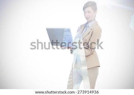 Confident businesswoman holding laptop against low angle view of skyscrapers - stock photo