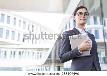 Confident businesswoman holding tablet PC outside office building - stock photo
