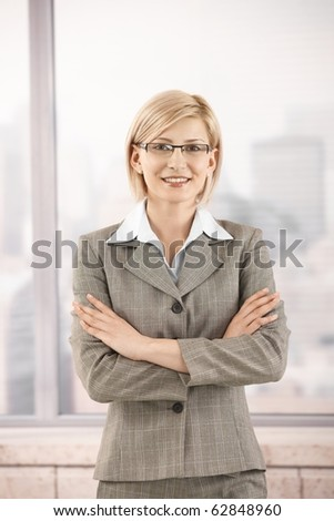 Confident businesswoman in office, smiling with arms folded.? - stock photo