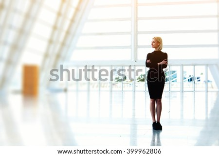 Confident businesswoman is standing in bought empty office space while is thinking about furnishings. Young beautiful female is standing with crossed arms in modern skyscraper interior with copy space - stock photo