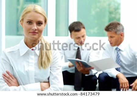 Confident businesswoman looking at camera at background of communicating men - stock photo