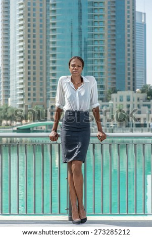 Confident businesswoman near the lake. African businesswoman businessman standing leaning on the handrail while standing near lake and looking at the camera - stock photo