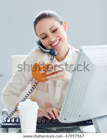 Confident businesswoman on phone eating a donut in the office - stock photo