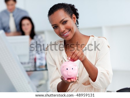 Confident businesswoman saving money in a piggy-bank at her desk - stock photo