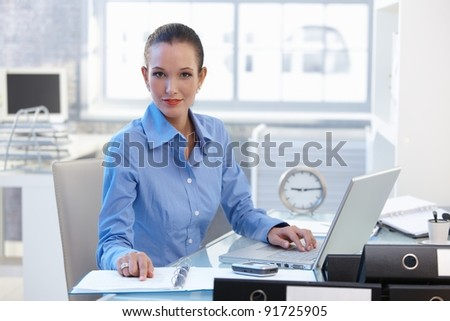 Confident businesswoman sitting at desk, smiling at camera.? - stock photo