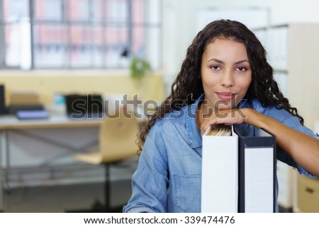 confident businesswoman sitting at the desk in the office leaning on folders
