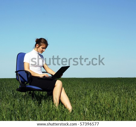 Confident businesswoman sitting in an armchair on the field