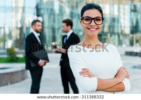 Confident businesswoman. Smiling young businesswoman keeping arms crossed and looking at camera while two her male colleagues talking to each other in the background - stock photo