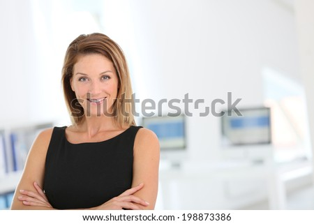Confident businesswoman standing in office - stock photo