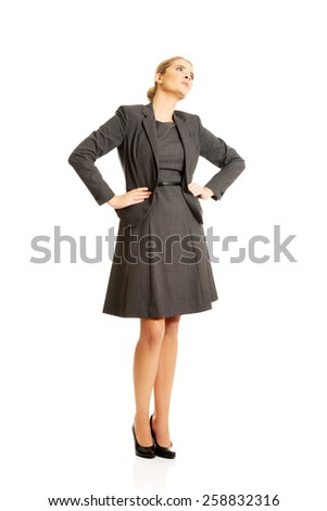 Confident businesswoman standing with her hands on hips. - stock photo