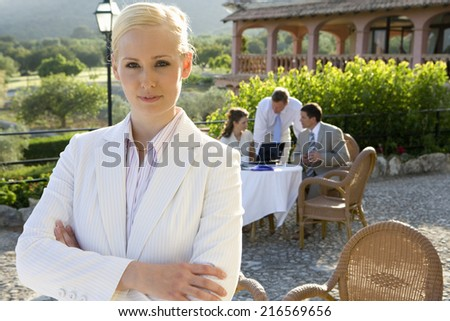 Confident businesswoman with arms crossed at caf�½ with coworkers in background - stock photo