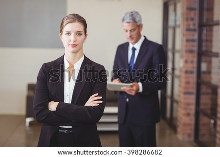 Confident businesswoman with arms crossed while male colleague standing in background - stock photo