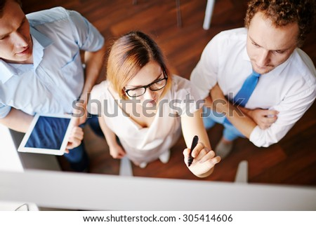 Confident businesswoman with highlighter pointing at board with two male colleagues near by - stock photo