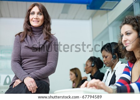 confident businesswoman with multiethnic group of female customer service representatives talking on the phone. Horizontal shape, waist up, front view - stock photo