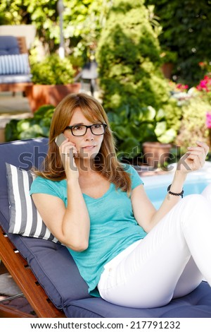 Confident casual woman with mobile sitting at garden.  - stock photo
