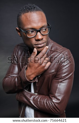 Confident casual young black man wearing brown leather jacket and glasses. Studio portrait against dark background.