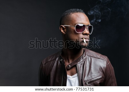 Confident casual young black man wearing brown leather jacket and sunglasses smoking cigarette. Studio portrait against dark background. - stock photo