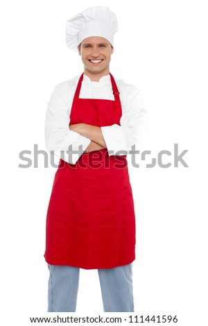 Confident cheerful male chef with arms crossed and smiling at camera - stock photo
