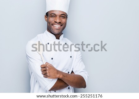 Confident chef. Cheerful young African chef in white uniform keeping arms crossed and smiling while standing against grey background - stock photo