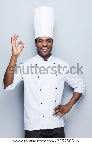Confident chef. Confident young African chef in white uniform gesturing OK sign and smiling while standing against grey background - stock photo