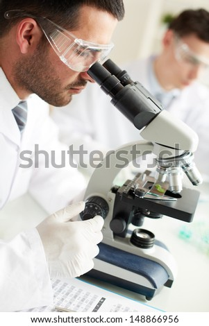 Confident clinician studying chemical elements in laboratory - stock photo