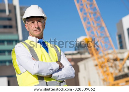 Confident construction engineer in hardhat with arms crossed on chest - stock photo