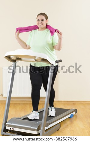 Confident corpulent woman running with perseverance on a treadmill