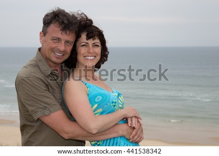 Confident couple hugging on beach on a holidays