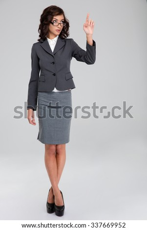 Confident curly pretty business woman in glasses and gray suit touching copyspace by finger and standing with crossed legs - stock photo