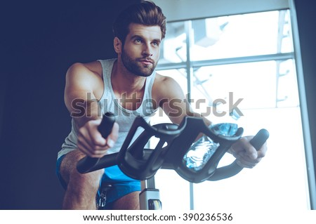Confident cycler. Low angle view of young man in sportswear cycling at gym - stock photo