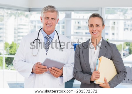 Confident doctor and pretty businesswoman smiling at camera in medical office - stock photo